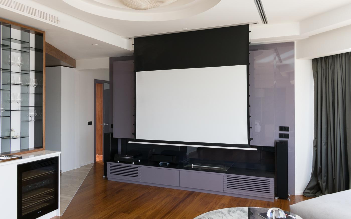 Домашний кинотеатр с проектором и экраном в квартире