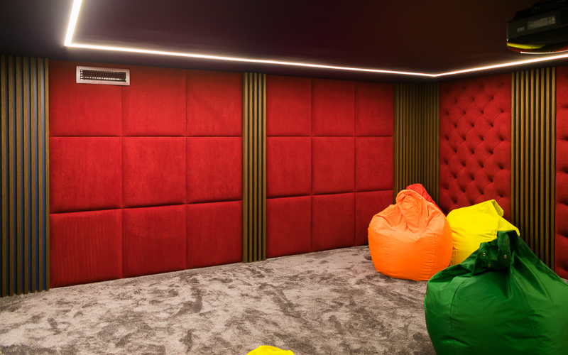 Тыловые акустические системы встроены в стену и замаскированы мягкими тканевыми панелями